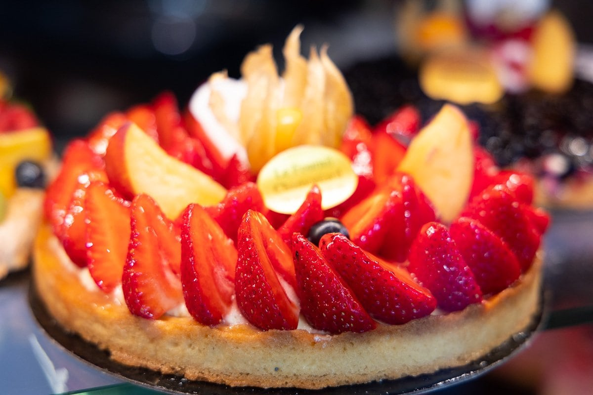 Horizontal closeup of a decorative fruit tart on display at a bakery (boulangerie) in Argentiére, France.