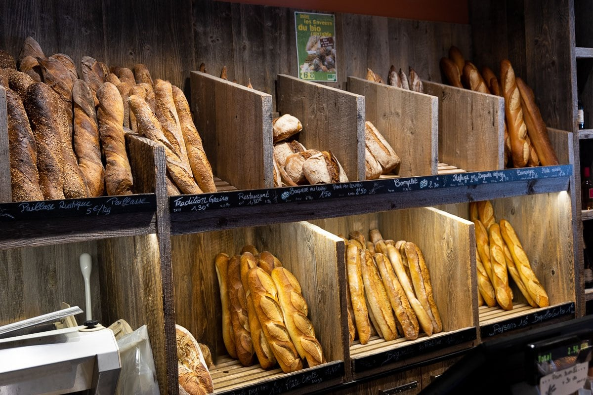 Horizontal photo of a daily display of various breads available in Argentiére's three bakeries (boulangeries).