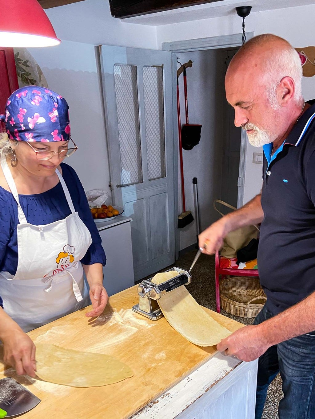 Vertical photo of Franca and Marcello creating the pasta for the meal.