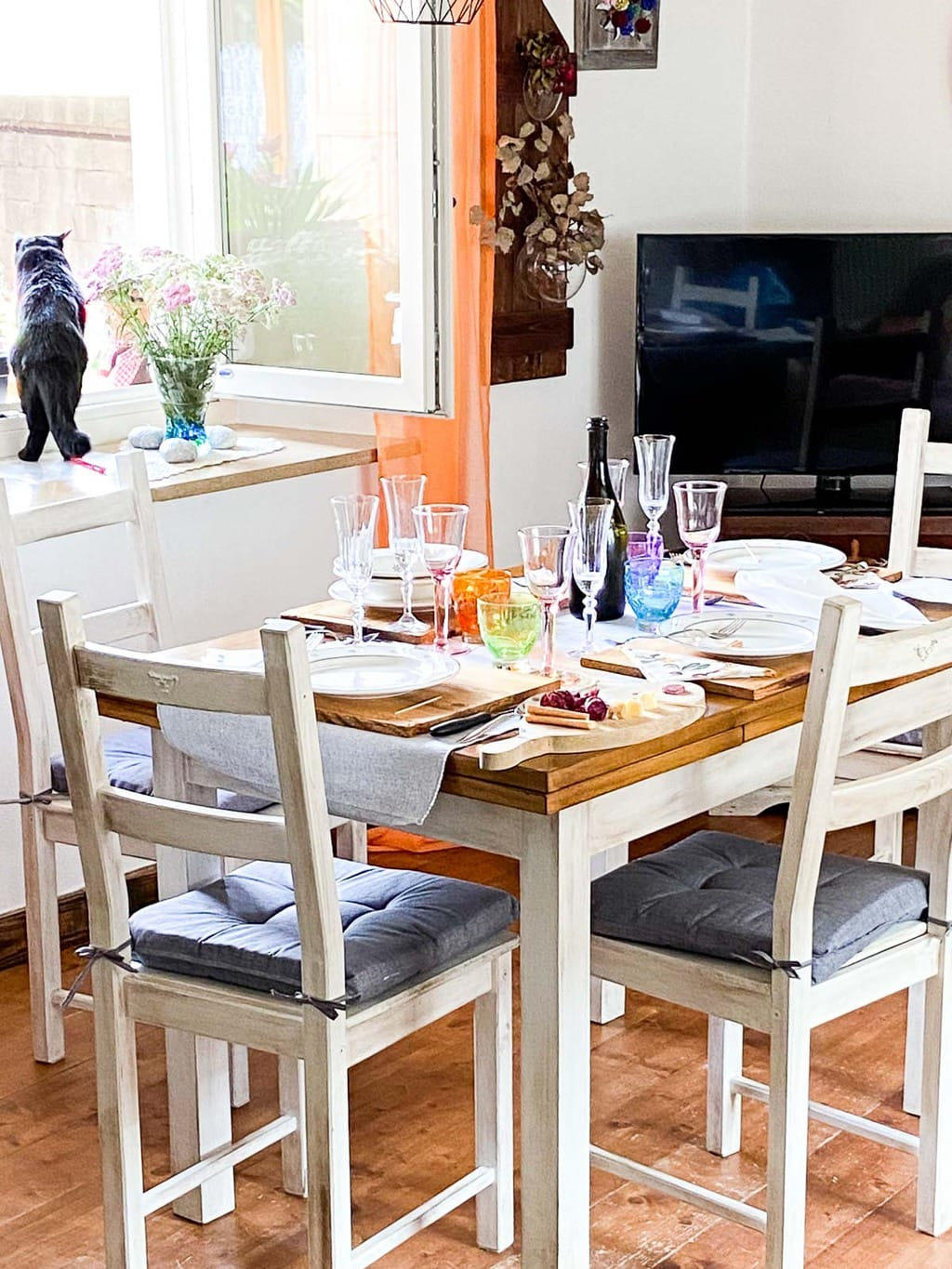 Vertical photo of the dining room table setting with Mirtillo, the family cat in the window.