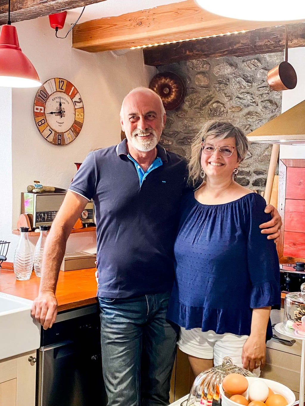 Vertical photo of Marcello and Franca in her Italian kitchen.
