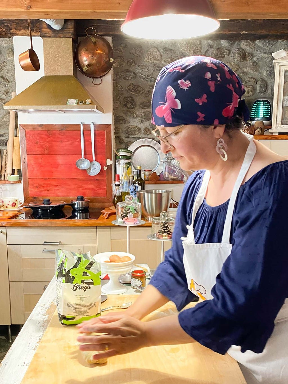 Vertical photo of Franca preparing the pasta dough in her Italian kitchen.