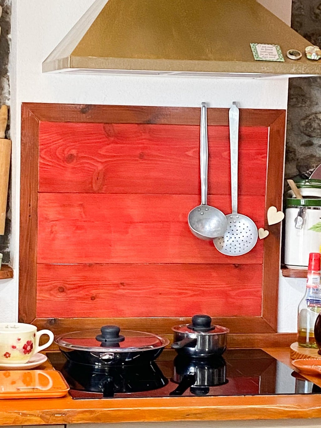 Vertical photo of Franca's stovetop in her kitchen with a colorful wood backsplash area and cooking tools.