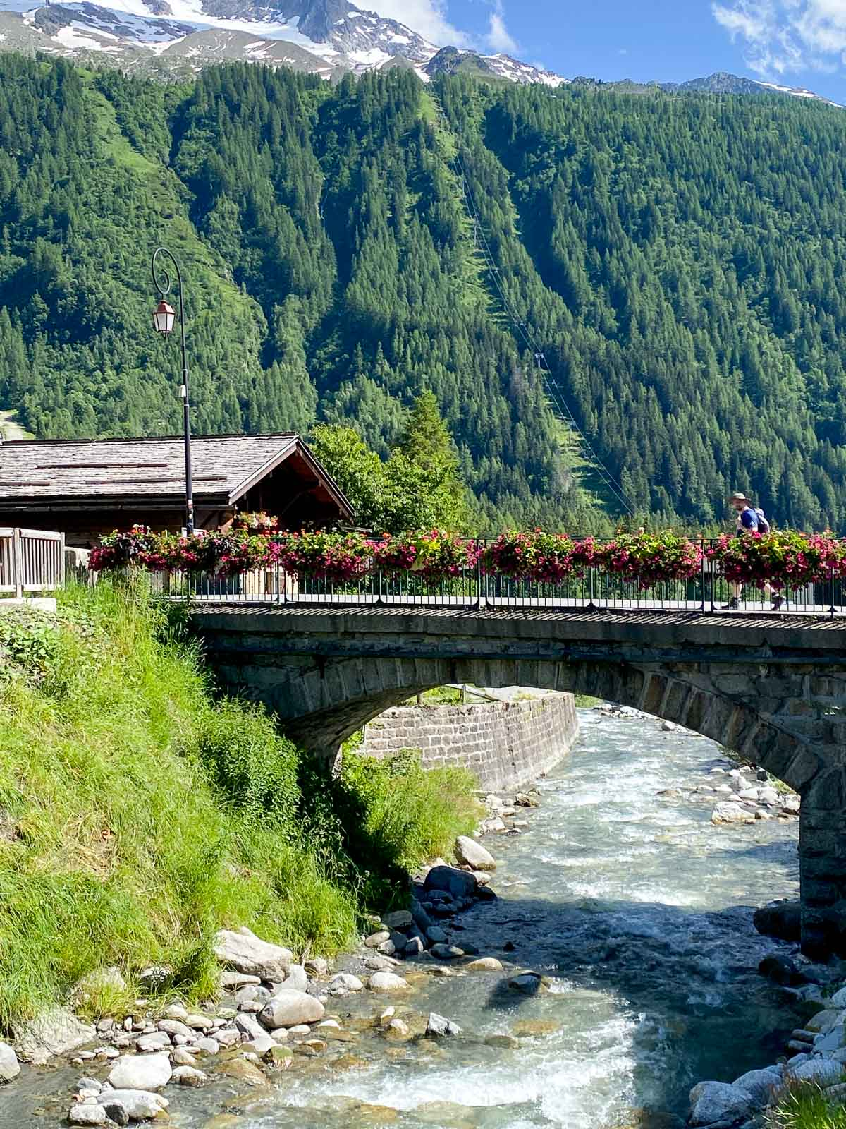 Vertical photo of the town bridge festooned with flowers over a mountain river in Argentiére, France.