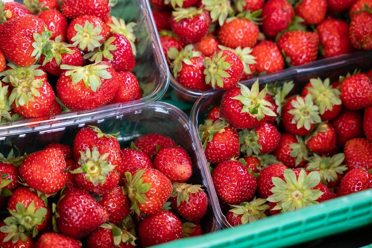 Horizontal closeup photo of containers of fresh strawberries at the artisan market.