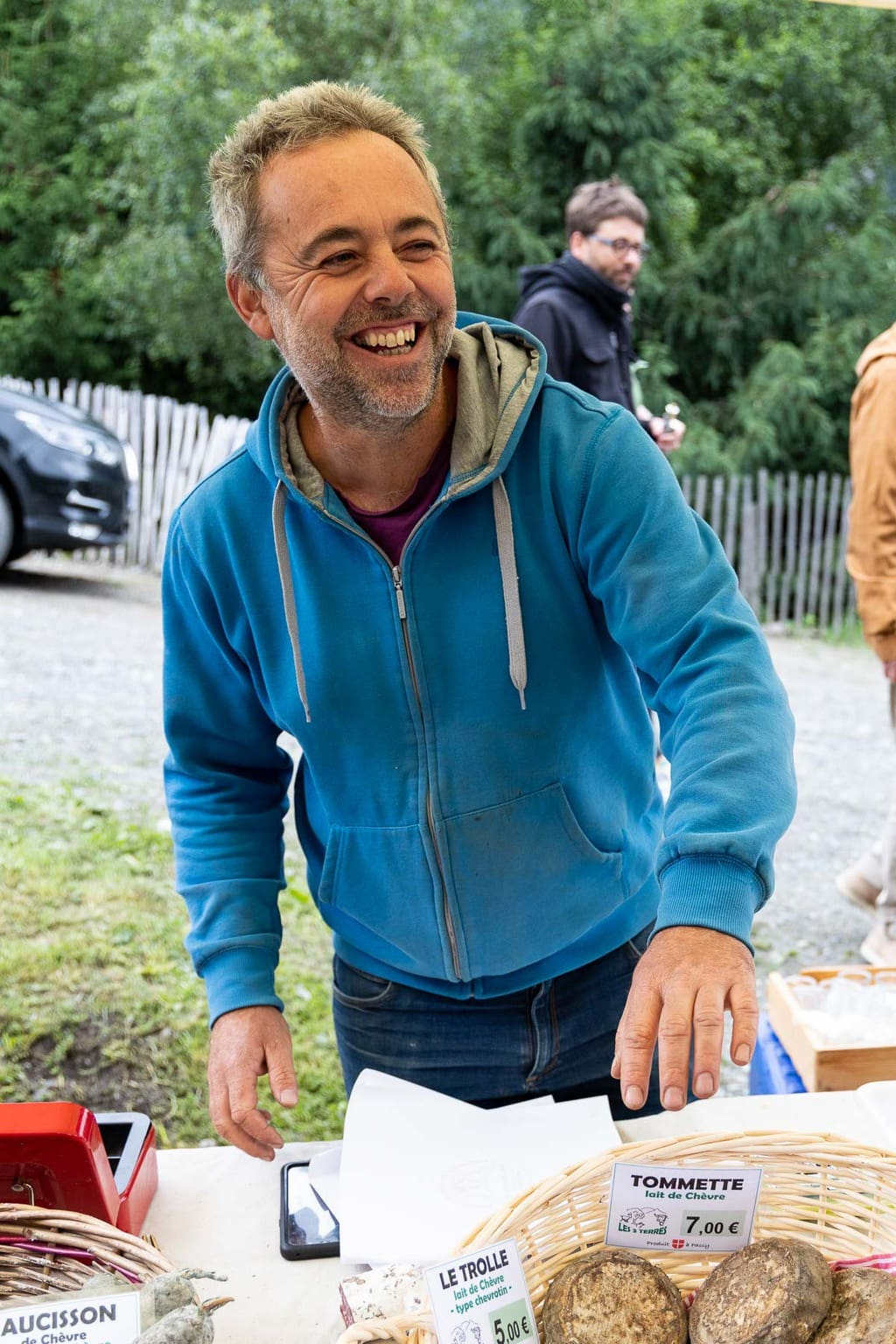 Vertical photo of Jerome Garcin, the sausage and cheese vendor at the artisan market in Les Houches, France.