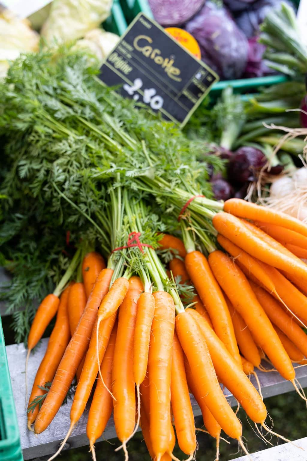 Vertical closeup photo of large bunches of carrots for sale at the artisan market in Les Houches, France.