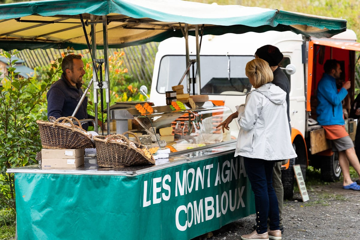 Horizontal photo of Chris and Emma exploring the artisan market products in Les Houches, France.