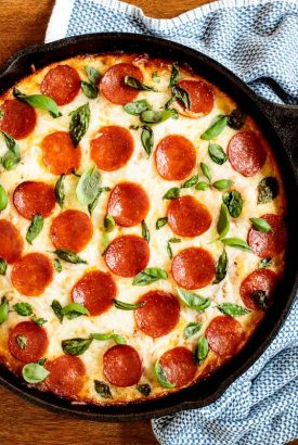 Horizontal overhead photo of an Easy Deep Dish Pepperoni Pizza in a black skillet on a wood table.