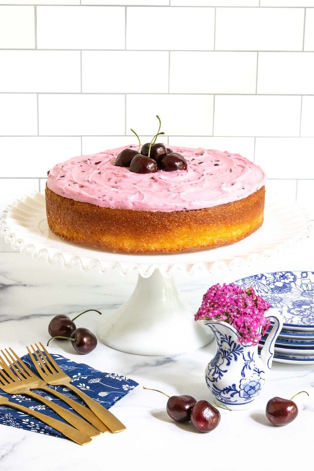 Vertical photo of a French Almond Cake with Cherry Buttercream on a white pedestal cake stand.