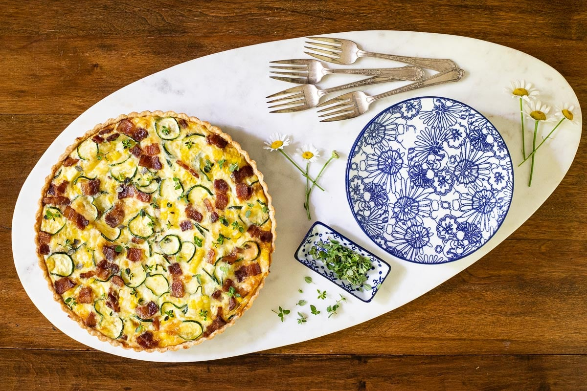 Horizontal overhead photo of an Easy Zucchini Summer Quiche on a white oval granite serving platter.
