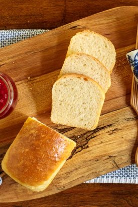 Horizontal overhead photo of Every Day Easy Brioche Bread on a wood cutting board with a slab of butter and a jar of raspberry jam.