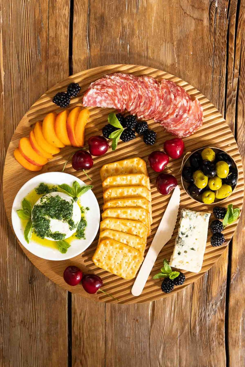 Horizontal overhead photo of a round wood charcuterie board featuring Italian Mint Pesto over goat cheese with crackers, cheeses, fruit, olives and sausage on a wood surface.