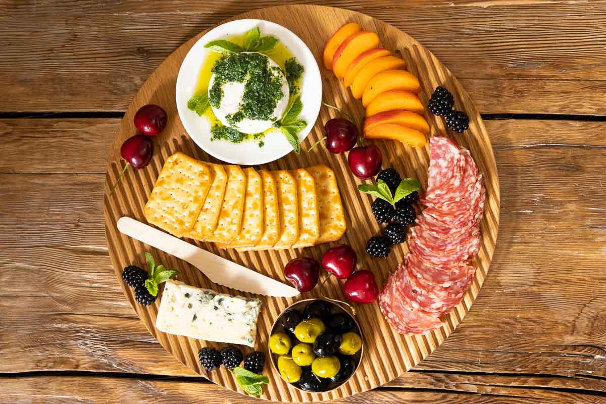 Horizontal overhead photo of a wood charcuterie board filled with crackers, olives, sausage, fruit and featuring Italian Mint Pesto on goat cheese.