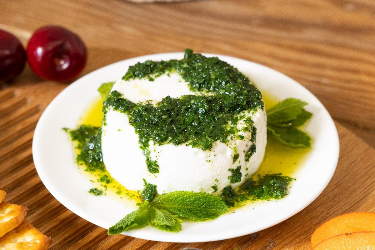 Horizontal extreme closeup photo of a white serving plate with Franca's Fabulous Italian Mint Pesto on top of a round slice of goat cheese.