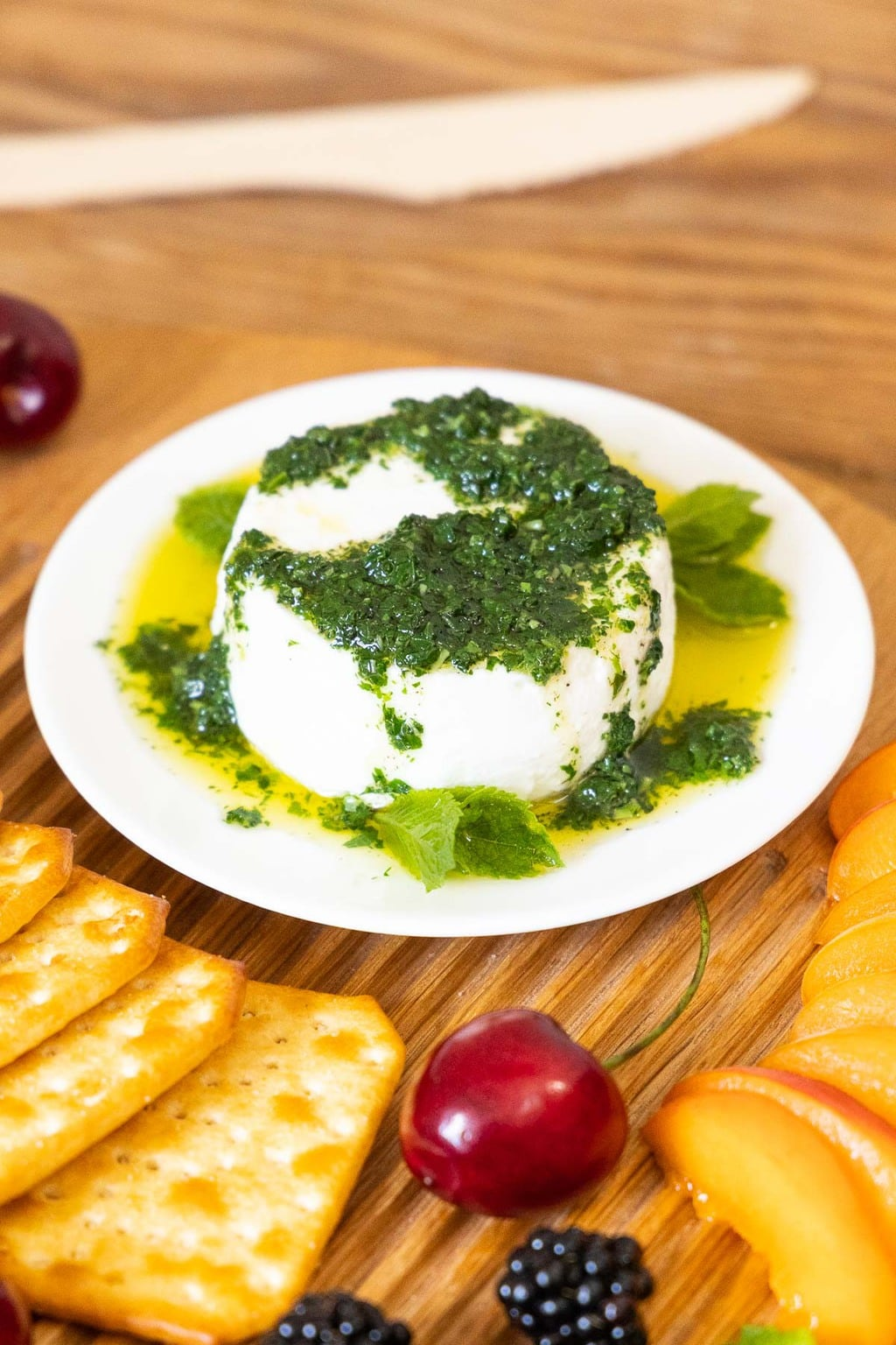 Vertical closeup photo of a round block of fresh goat cheese with Franca's Italian Mint Pesto and olive oil drizzled over the top.