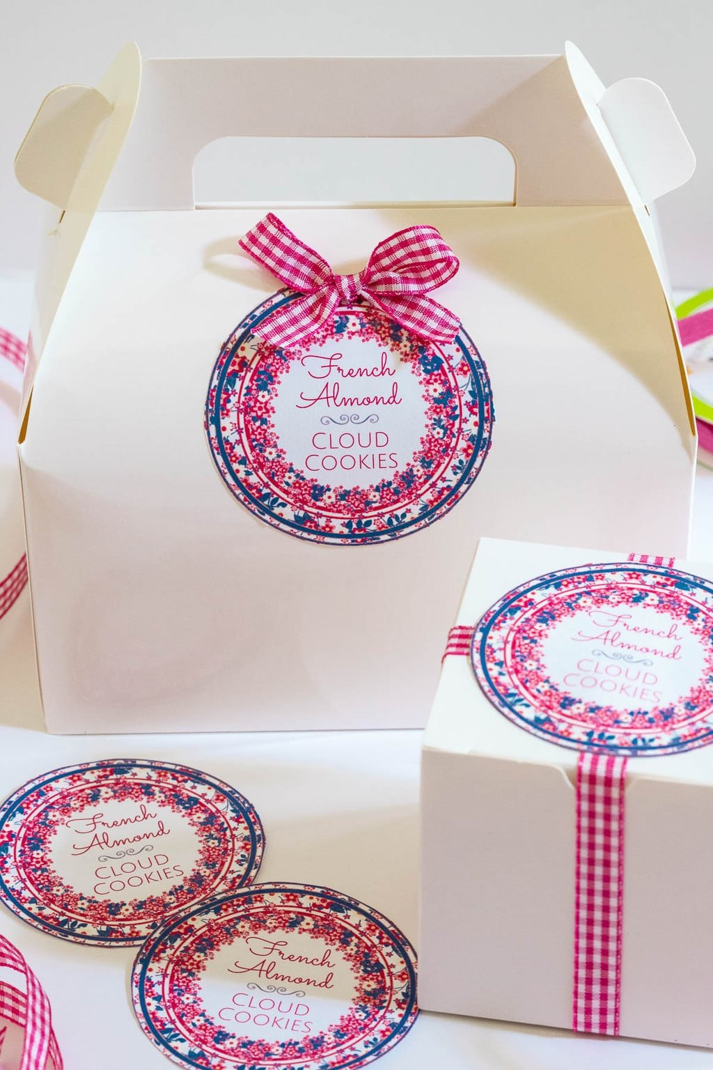 Vertical photo of Ridiculously Easy French Almond Cookie gift boxes with custom cookie labels on the boxes.
