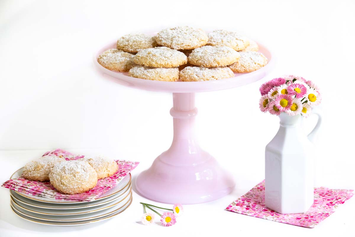 Horizontal photo of a batch of Ridiculously Easy French Almond Cookies on a pink serving pedestal stand and on pink and white napkins.