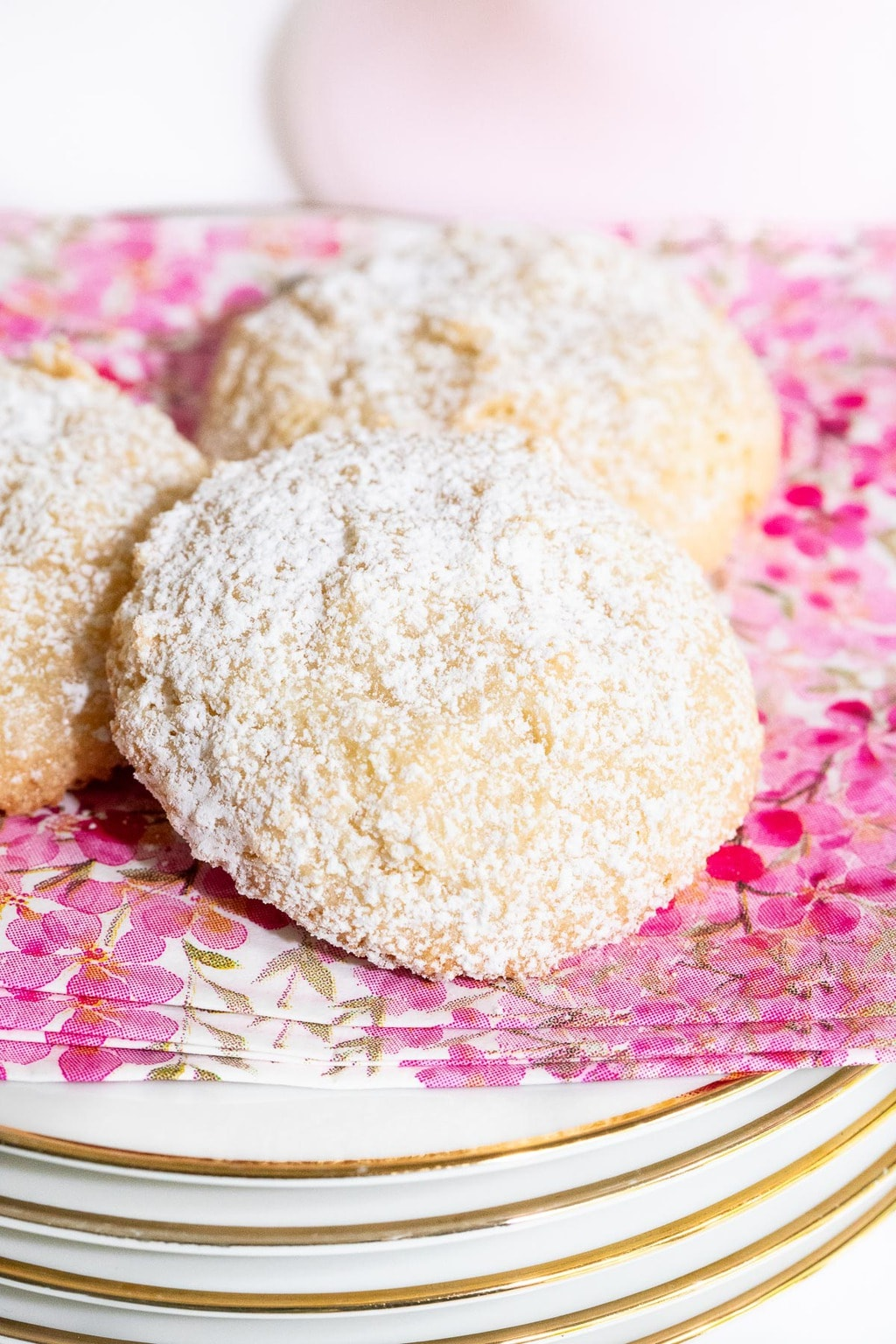 Vertical closeup photo of a plate of Ridiculously Easy French Almond Cookies on a pink, white and gold napkin.