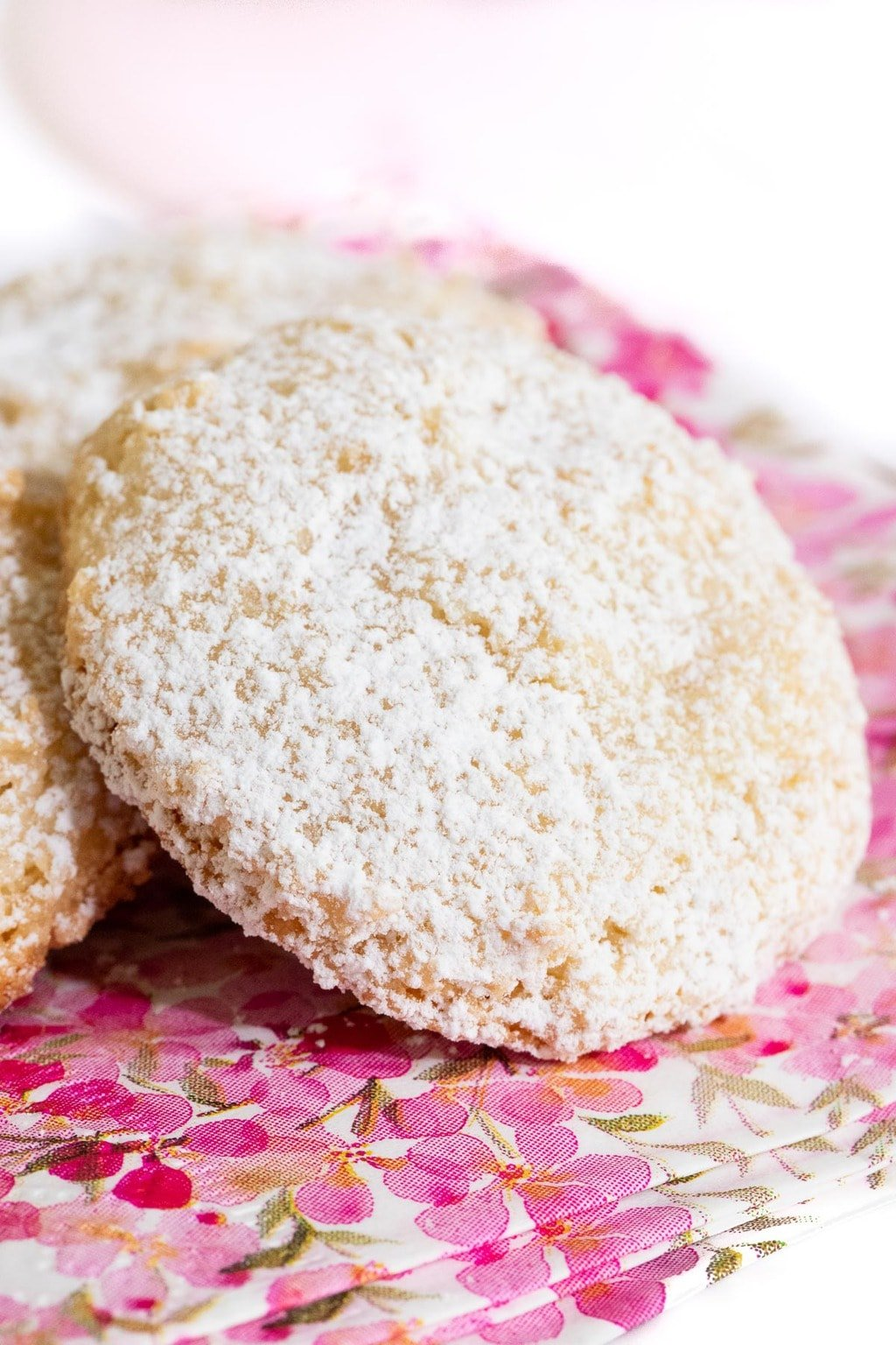 Vertical extreme closeup photo of a Ridiculously Easy French Almond Cookie covered in powdered sugar on a pink, white and gold napkin.