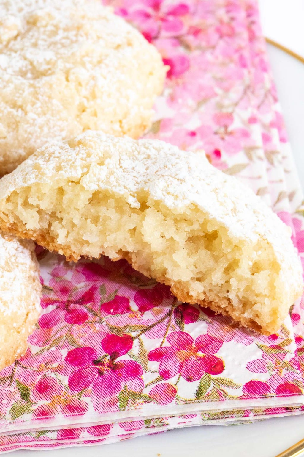 Vertical extreme closeup photo of the inside of a Ridiculously Easy French Almond Cookie on a pink, gold and white patterned napkin.