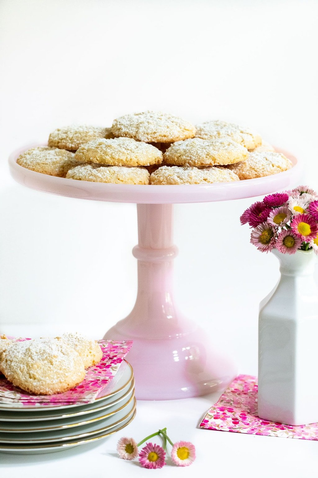 Vertical photo of a batch of Ridiculously Easy French Almond Cookies on a pink pedestal serving plate.