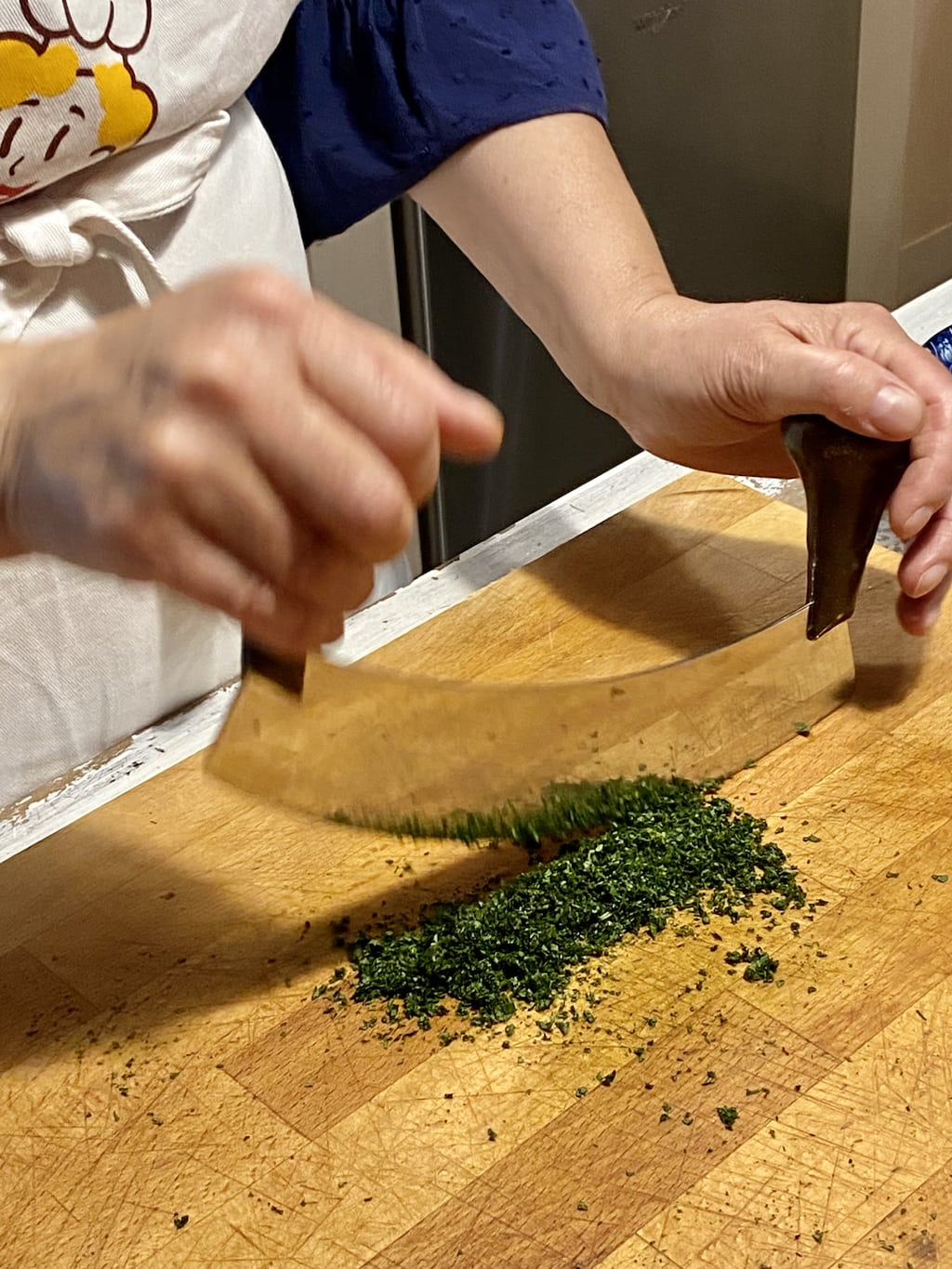 Vertical closeup photo of Franca chopping the mint leaves extra fine with a mezzaluna on a wood cutting board.