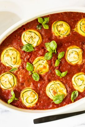 Horizontal overhead photo of a white baking dish of Make-Ahead Italian Zucchini Involtini.