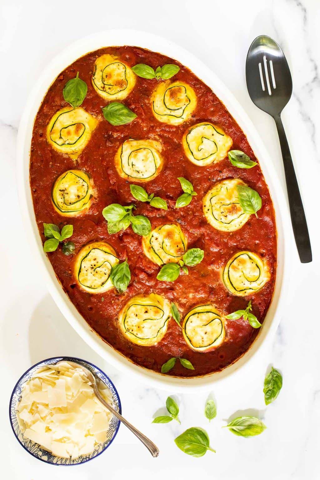 Vertical overhead picture of Zucchini Involtini in a white oval baking dish