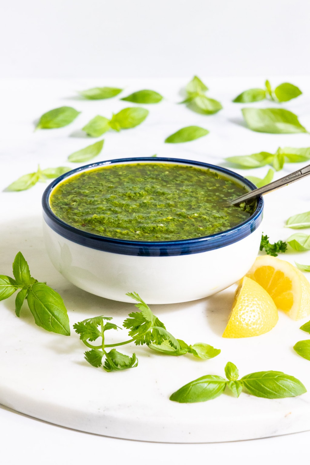 Vertical picture of Chimichurri Sauce in a white bowl on a white background with fresh basil leaves