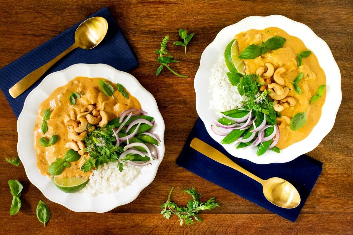 Horizontal overhead photo of two serving bowls of 30-Minute Basil Coconut Chicken garnished with fresh basil leaves and lime wedges on a wood table.