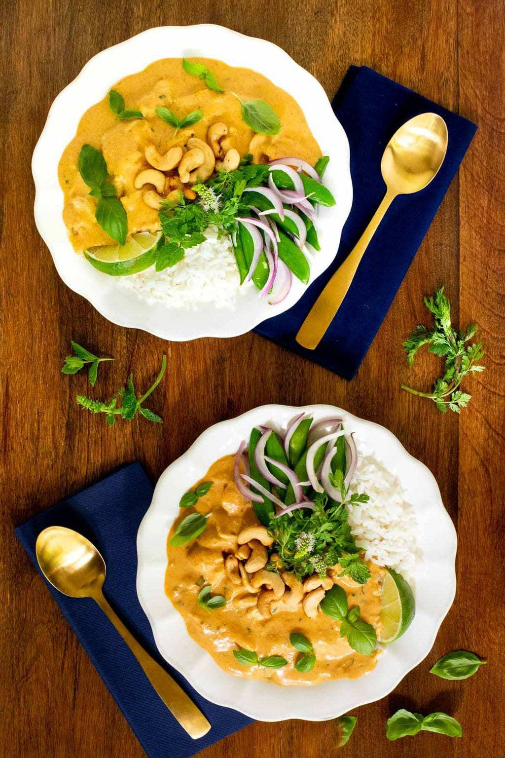 Vertical overhead photo of two individual serving bowls of 30-Minute Basil Coconut Chicken on a wood table.