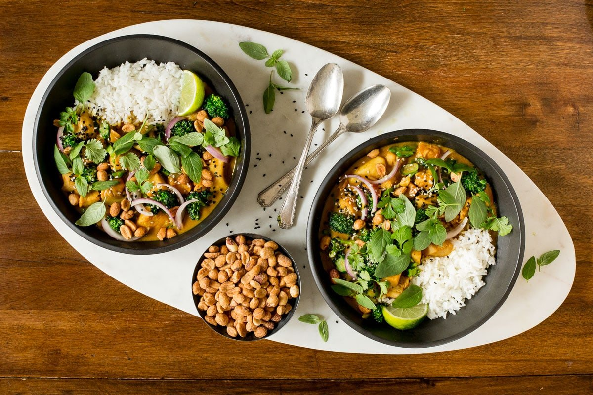 Overhead horizontal photo of two black serving bowls of 30 Minute Thai Peanut Chicken on an oblong marble surface.