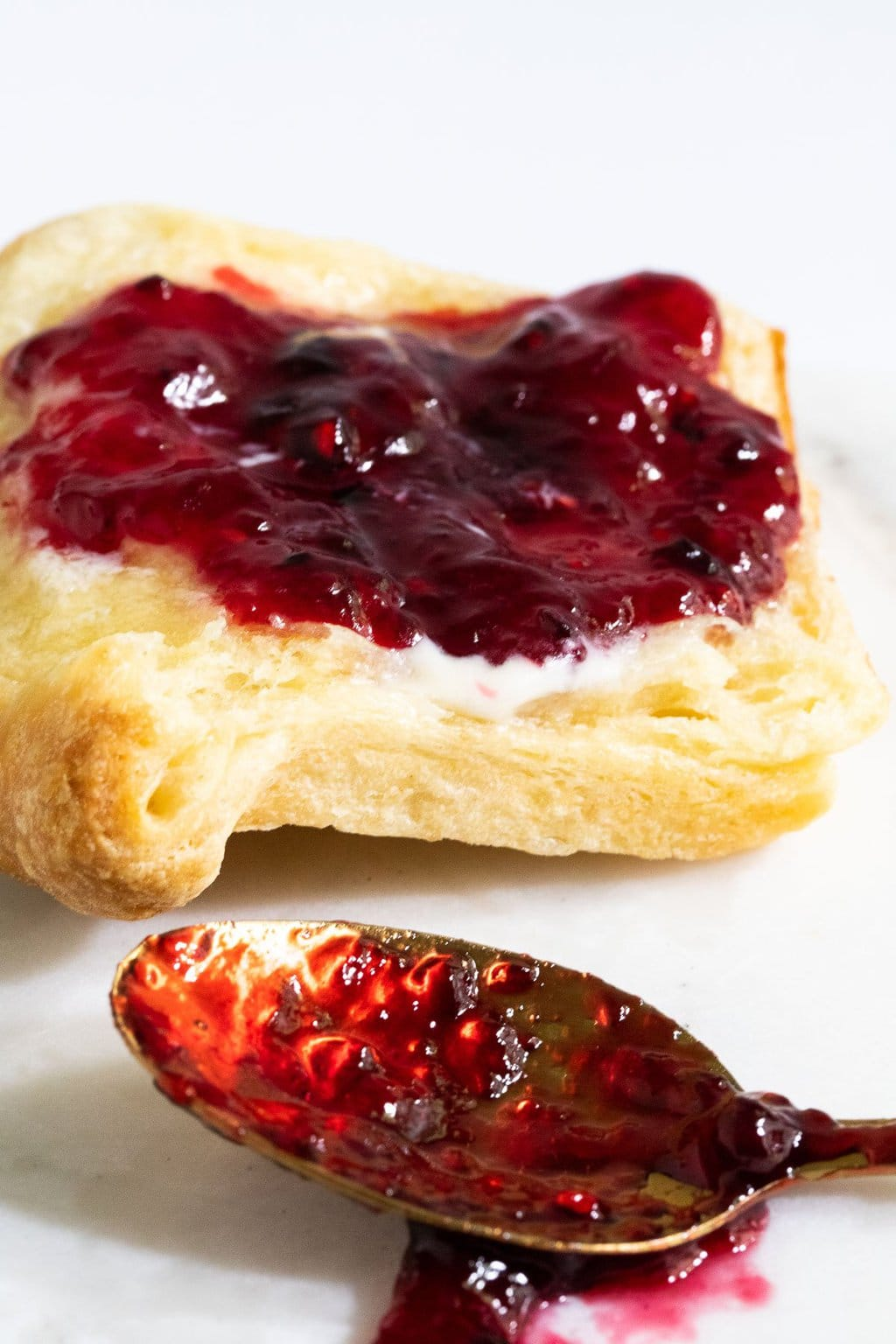 Vertical extreme closeup photo of Easy 30-Minute Blackberry Freezer Jam on a slice of fresh brioche bread.
