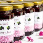 Horizontal closeup photo of a diagonal row of jars of Blackberry Freezer Jam.