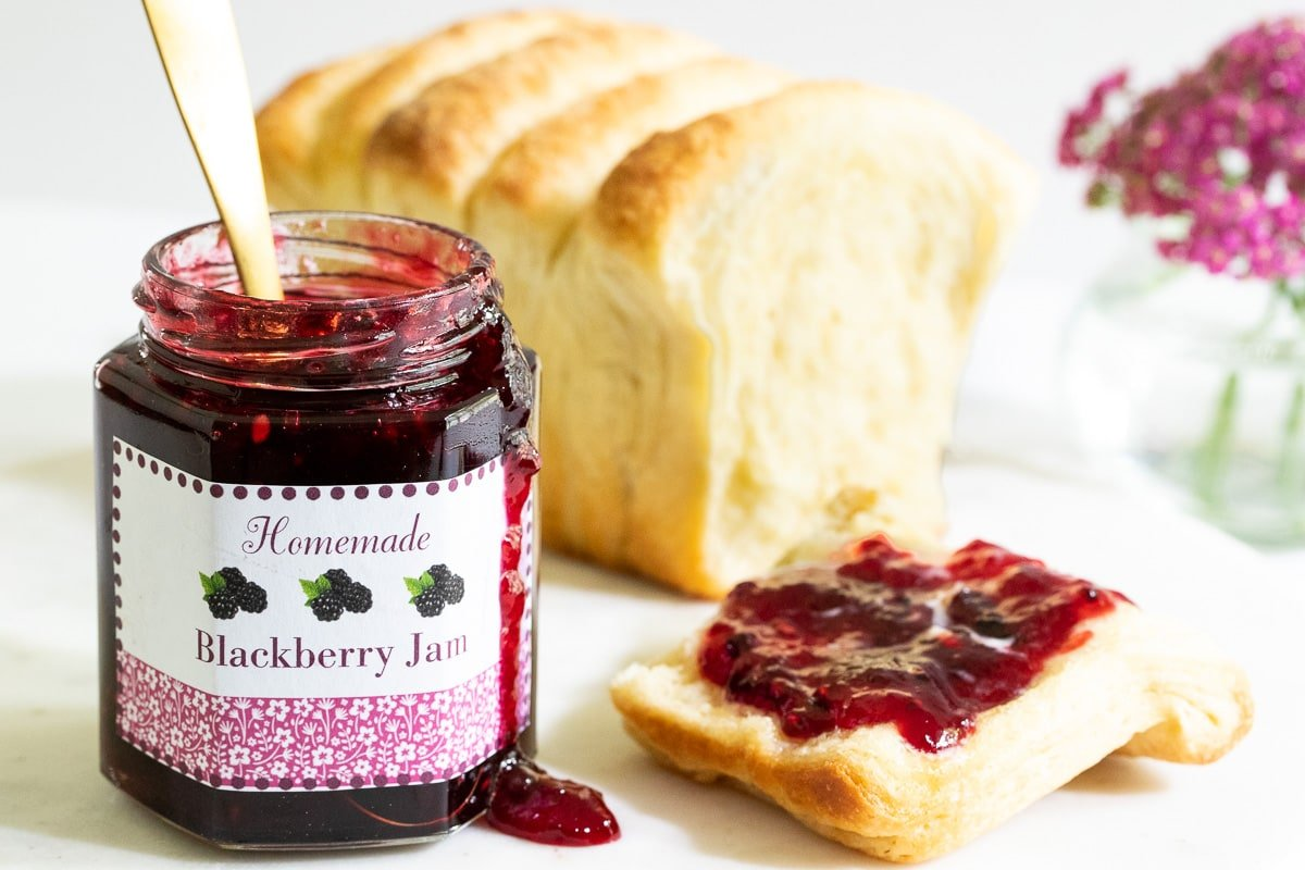 Horizontal closeup photo of Easy 30-Minute Blackberry Freezer Jam with custom labels for gift giving.