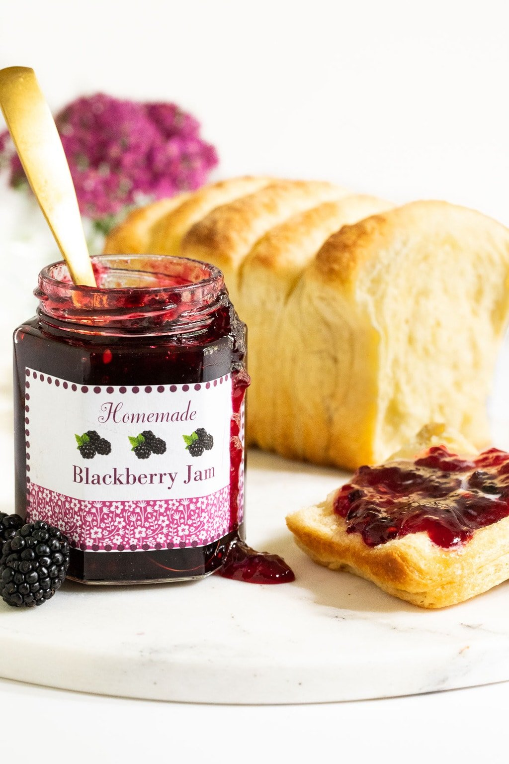 Vertical closeup photo of a jar of Easy 30-Minute Blackberry Freezer Jam. A slice of bread with jam on top is next to the jar and a loaf of homemade brioche bread is in the background.