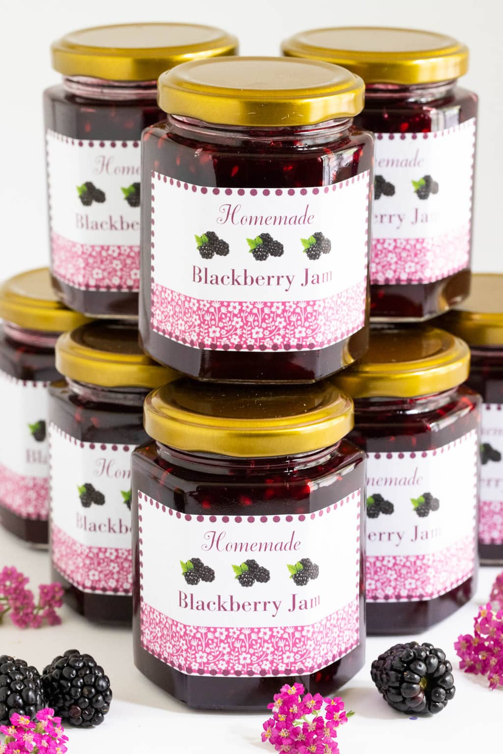 Vertical photo of stack of Blackberry Freezer Jam with custom gift labels attached to each jar.