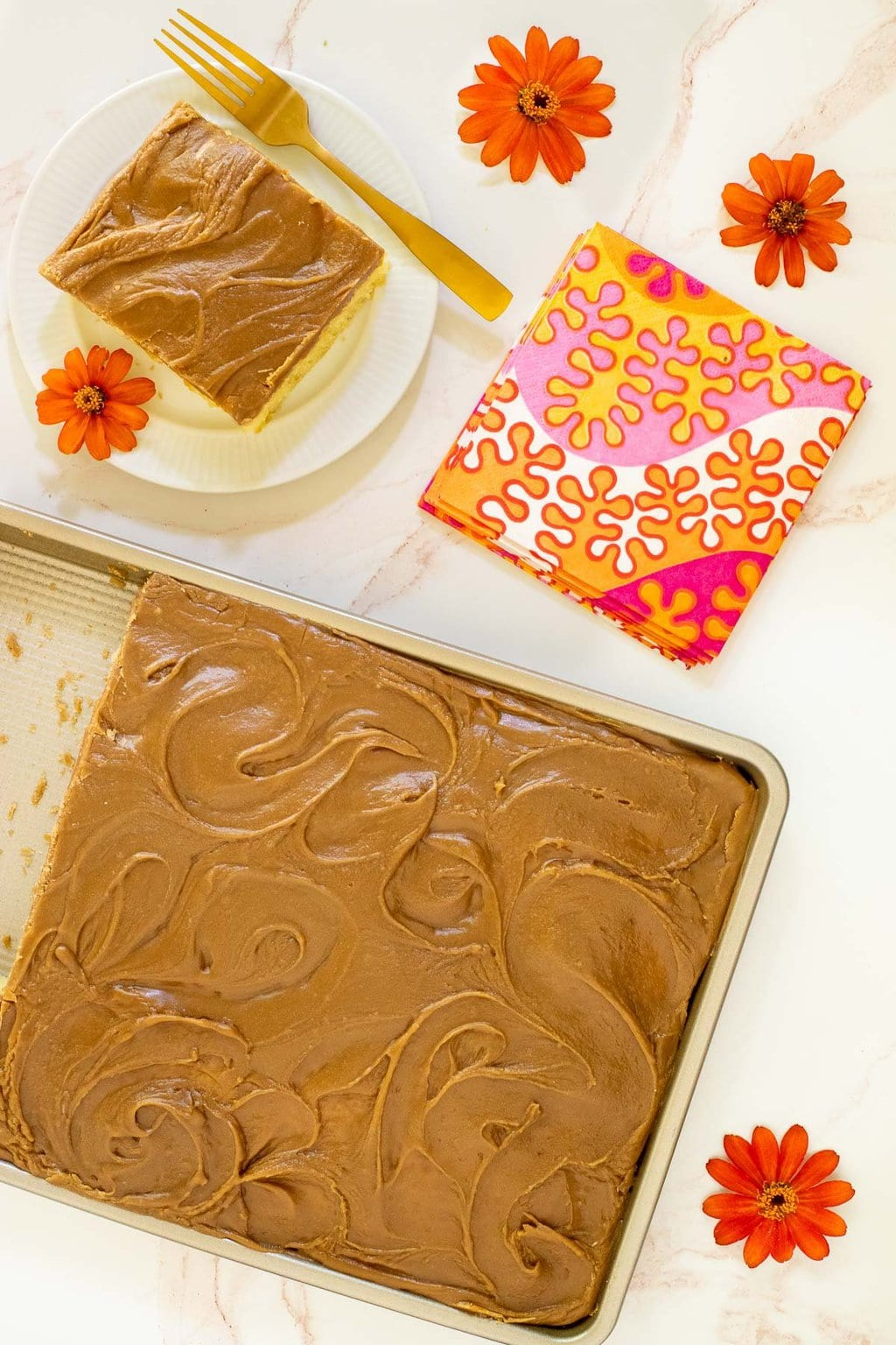 Vertical overhead photo of a Ridiculously Easy Caramel Buttermilk Sheet Cake with an individual slice on a small white serving plate.