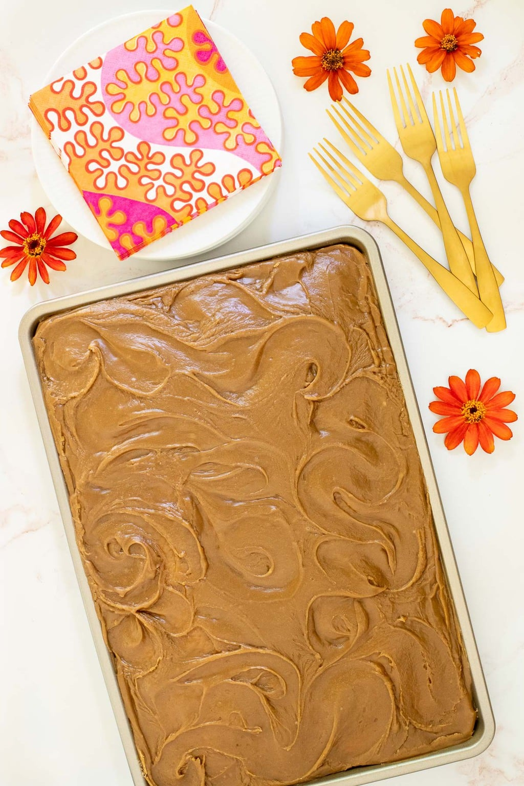Vertical overhead photo of a Ridiculously Easy Caramel Buttermilk Sheet Cake on a white marble surface surrounded by orange zinnia flowers.