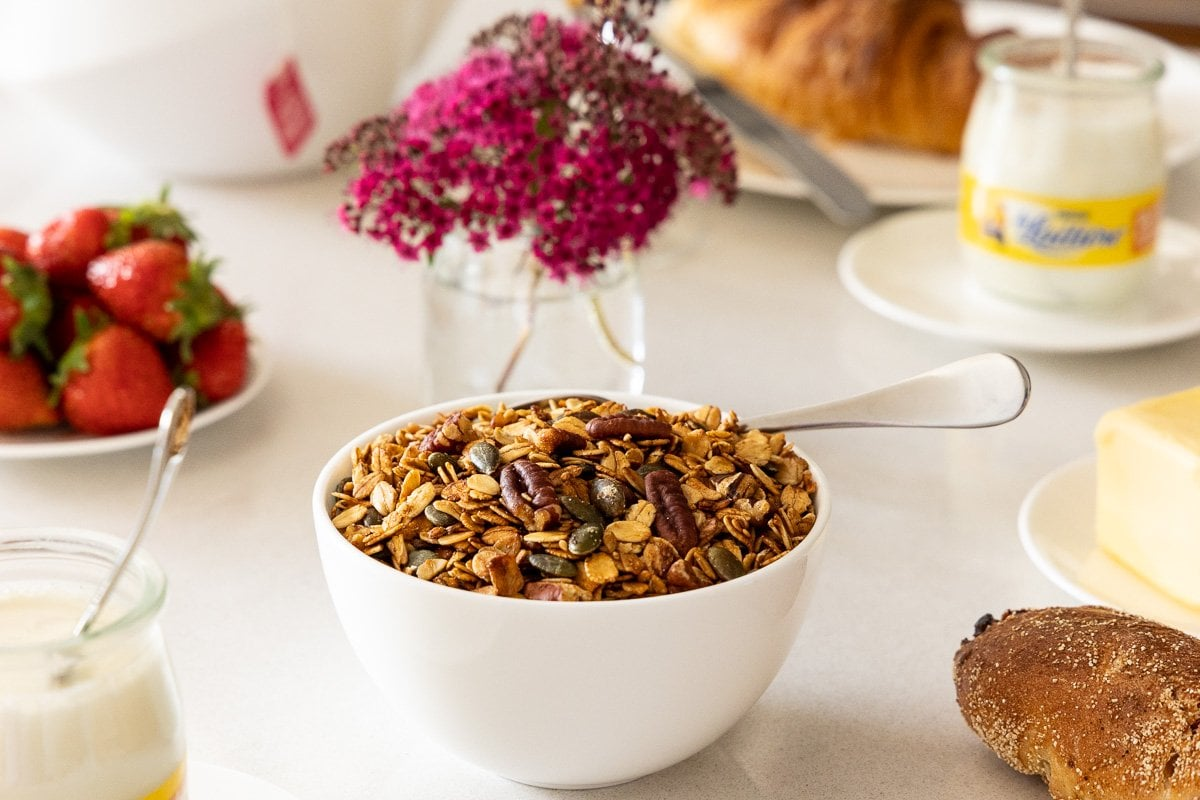 Closeup horizontal photo of stovetop pumpkin seed granola surrounded by other breakfast items.
