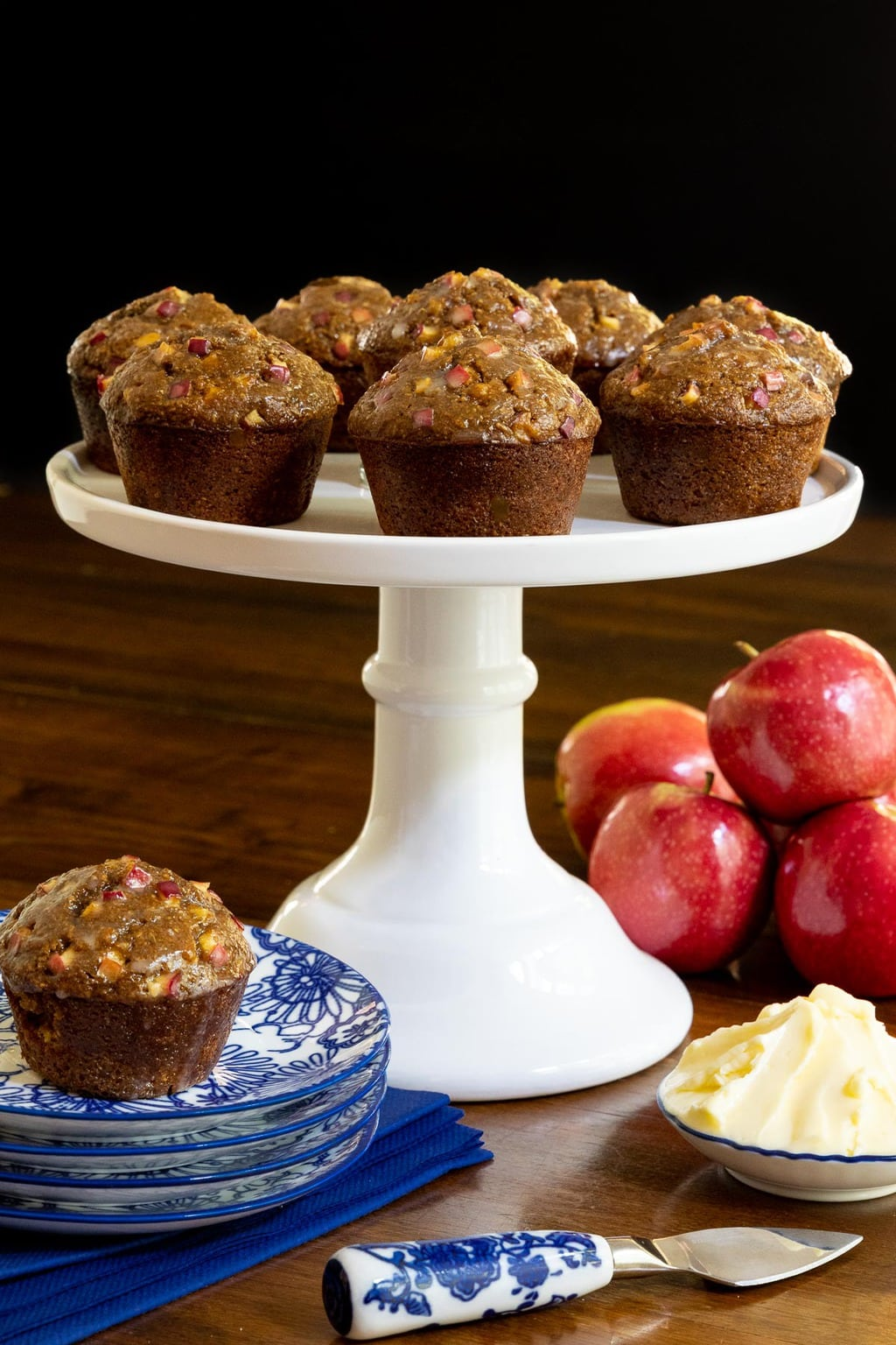 Horizontal photo of a batch of Honey-Glazed Apple Bran Muffins on a white pedestal plate surrounded by fresh apples and additional muffins.