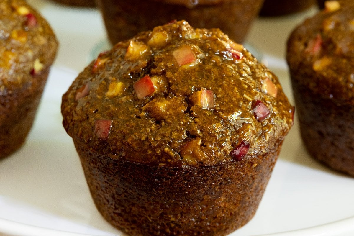 Horizontal closeup photo of a Honey-Glazed Apple Bran Muffin with more muffins in the background.
