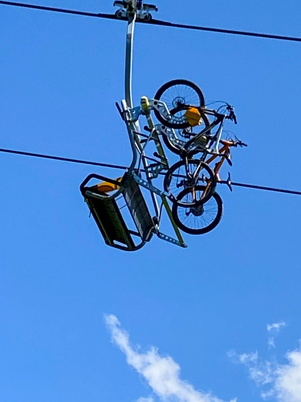 Vertical photo of mountain bikes being transported on a chair lift just above Le Tour, France.