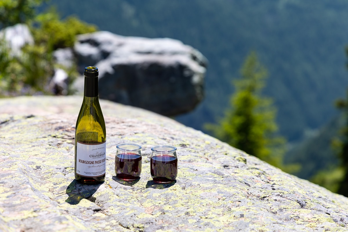 Horizontal photo of a bottle of French wine and two yogurt glasses filled with wine on a rock in the French Alps.