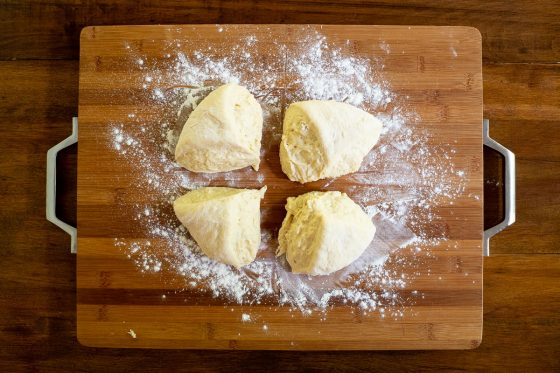 Overhead horizontal process photo of No Knead Pull-Apart Brioche Bread dough divided into four equal parts