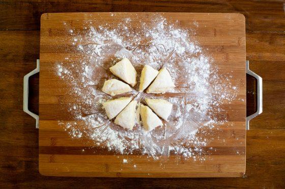 Overhead horizontal process photo of No Knead Pull-Apart Brioche Bread dough cut into eight pieces.