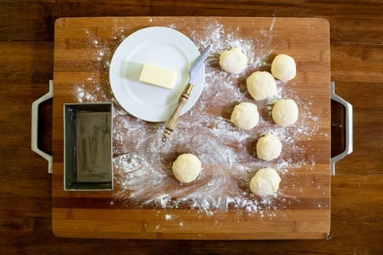Horizontal overhead process photo of No Knead Pull-Apart Brioche Bread dough rolled into eight individual balls.