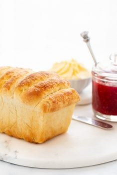 Vertical photo of a loaf of No Knead Pull-Apart Brioche Bread with a jar of raspberry jam and a dish of fresh butter in the background.