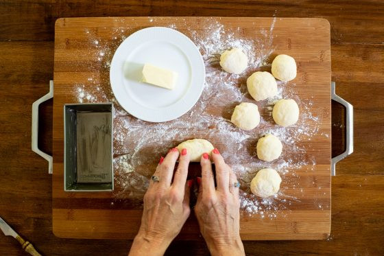 Overhead horizontal process photo of No Knead Pull-Apart Brioche Bread dough being flattened to make the individual parts of the bread.